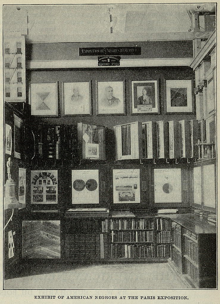 Photo of exhibit table with charts, graphs and photos mounted in frames along three walls, depicting elements Black American life during the late 19th and early 20th centuries.